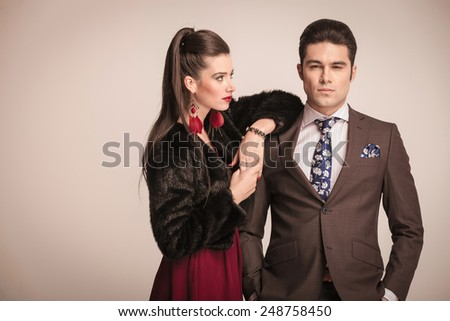 Handome young business man holding both hands in pocket while his girlfriend is looking and leaning on him.