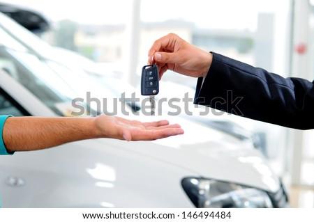 Handover of car keys in a dealership - stock photo