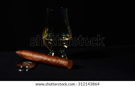 Handrolled cuban cigar whit a glass of single malt whiskey isolated over black background - stock photo
