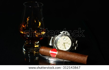 Handrolled cuban cigar whit an elegant wristwatch isolated over black background
