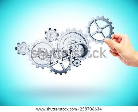 hands adds to the gear mechanism on blue background - stock photo