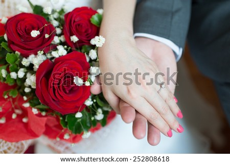 Hands and diamond ring on wedding bouquet - stock photo