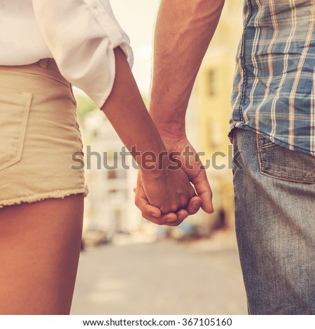 Hands and hearts together. Close-up of loving couple holding hands while walking outdoors - stock photo