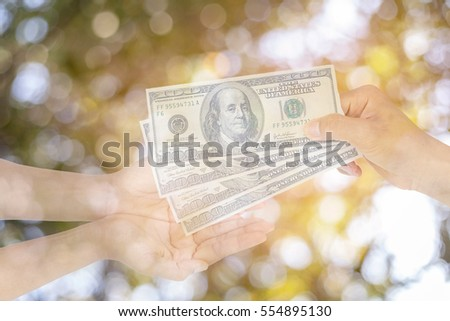 Hands and money on autumn background and sunlight bokeh