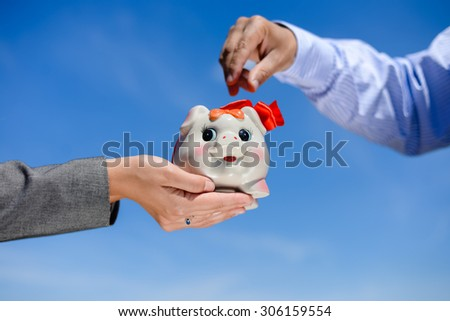 Hands and piggy bank over blue sky sunny outdoors background copy space - stock photo