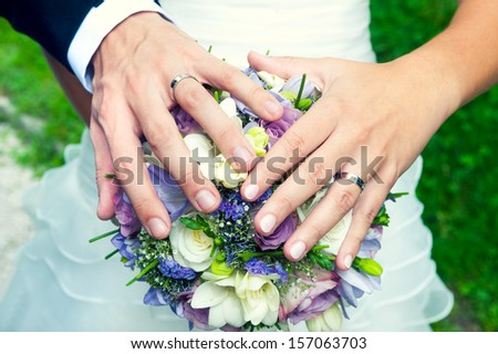 Hands and rings on wedding bouquet, close up