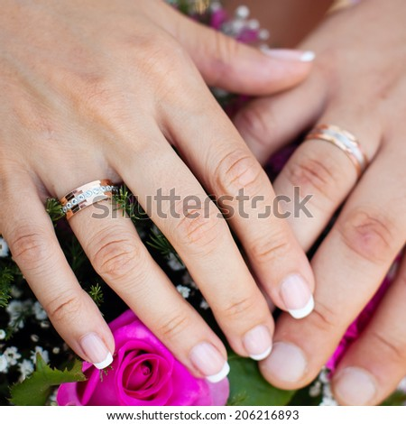 Hands and rings on wedding bouquet. wedding theme background