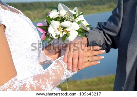 Hands and rings with wedding bouquet against a river