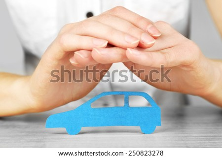 Hands and toy car. Protection of car concept - stock photo