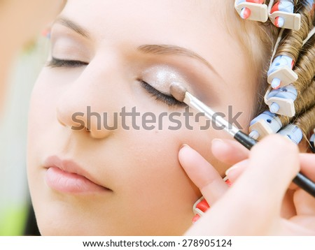 hands applying make up on a woman head