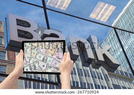 Hands  are holding tablet, whose screen contains a background of U.S. banknotes. Background of the photo is composed a glass wall of office building with the inscription Bank.  - stock photo