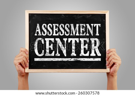 Hands are holding the blackboard of Assessment center against gray background. - stock photo