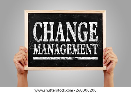 Hands are holding the blackboard of Change management against gray background. - stock photo