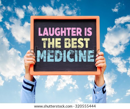 Hands are holding the blackboard of message Laughter is the Best Medicine - stock photo