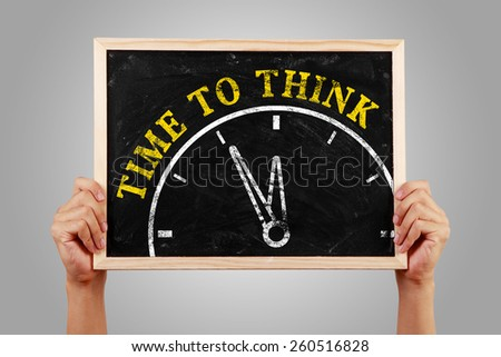 Hands are holding the blackboard of time to think concept against gray background. - stock photo