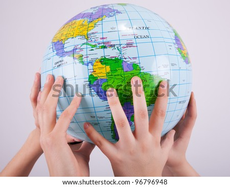 Hands are holding up a globe