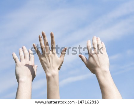 hands are lifted to a blue cloudy sky - stock photo
