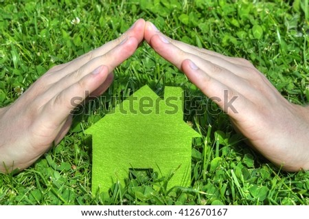 Hands are making roof on top of the house icon standing on the grass
