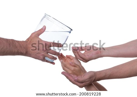 Hands are reaching out to clean drinking water which is served to them - stock photo