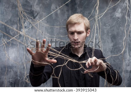 Hands are tied. Young man in  black suit got caught on the web. Concept of manipulation and slavery