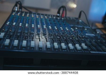 hands at a sound mixing console. MIxer and sound board at a show. Detail of a concert mixer, mixer to control the volume and music, exploration and entertainment. sound studio record equipment
