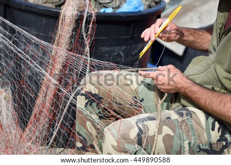 hands at work on fishing net with tool