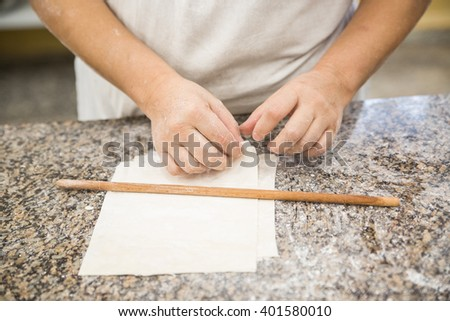 Hands baking dough with rolling pin on wooden table