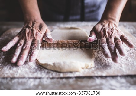Hands baking dough with rolling pin on wooden table, depth of field  - stock photo