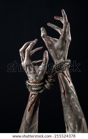 Hands bound,bloody hands, mud, rope, on a black background, isolated, kidnapping, zombie, demon - stock photo
