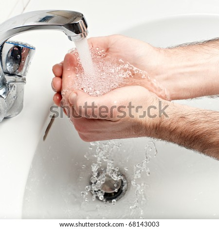 hands catching falling water closeup - stock photo