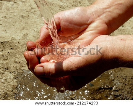 hands catching the stream of water - stock photo