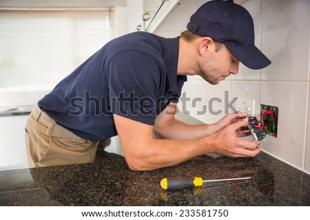 Hands checking the connections of electrical cables in the kitchen - stock photo