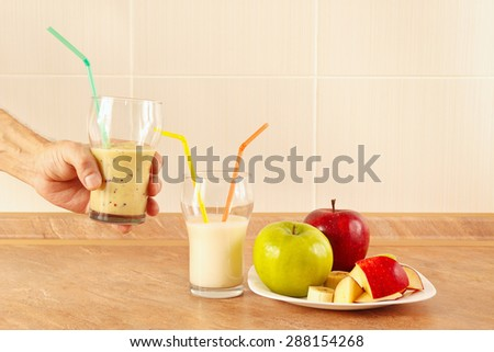 Hands chef offers a multyfruit cocktail in glasses - stock photo