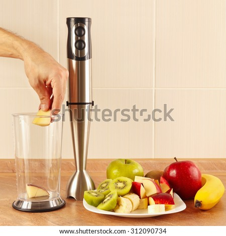 Hands chefs put the fruit in the blender - stock photo