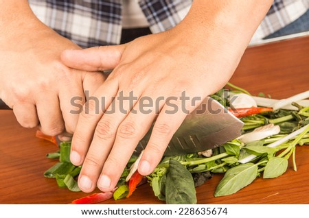 hands chopping food pepper mushrooms herbs with big knife on wooden table closeup