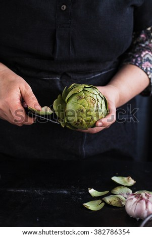 Hands clean and cut fresh artichoke with knife on a dark table. Mothers hands preparing Artichoke hearts. Creative idea. Country dark styling. - stock photo