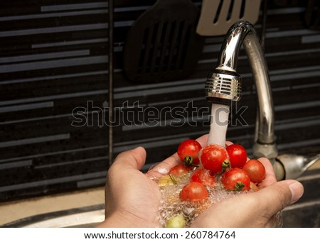 Hands cleaning tomato under the water Tap. Healthy concept.focus on tap,on isolated white Background. - stock photo
