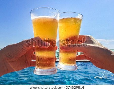 Hands Clinking Glasses of Beer by the pool - stock photo