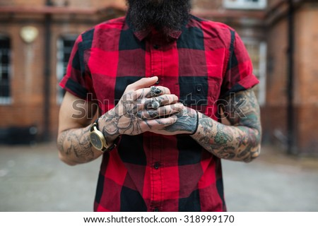 Hands close up of young tattooed man portrait in Shoreditch borough, London. Hipster style. - stock photo