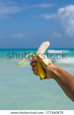 Hands close up of young woman holding a banana at the beach  - stock photo