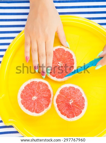 Hands close up of young woman with watermelon manicure cutting grapefruit, summer manicure nail art and food concept  - stock photo