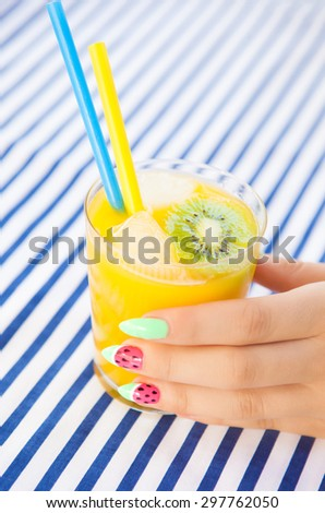 Hands close up of young woman with watermelon manicure holding glass of orange juice, manicure nail art concept  - stock photo