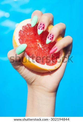 Hands close up of young woman with watermelon manicure holding slice of grapefruit summer manicure nail art and food concept  - stock photo