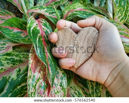 Hands clutching a heart made of stone with a background of colorful leaves, Hand squeezing a heart made of stone