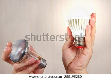 Hands compared incandescent bulb and glowing ecofriendly led lamp on a light wood background - stock photo