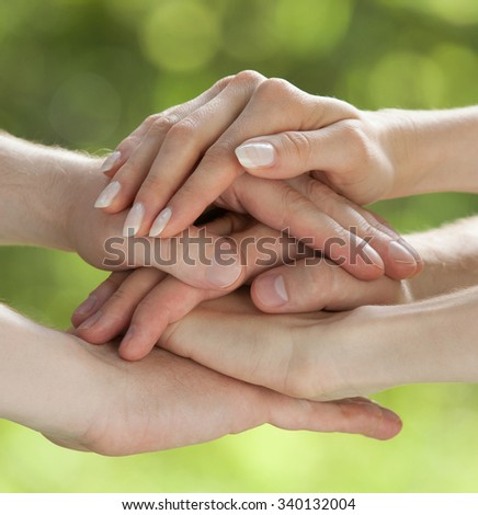 Hands connected together on light green background - concept of united team - stock photo