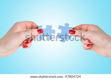 hands  connecting different pieces of blue puzzle - stock photo