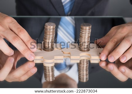 Hands connecting puzzle pices with coins at the table