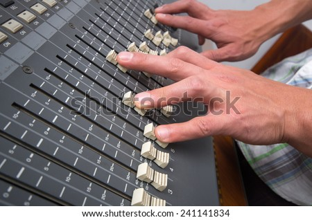hands controlling professional studio mixing console closeup shot - stock photo