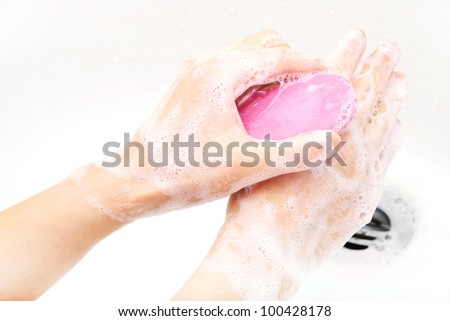 hands covered with soap being washed in the sink - stock photo